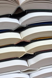 Several thick hardcover books stacked on top of each other